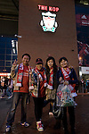 Three Liverpool supporters from China posing for a photograph outside the Kop at Anfield, before their team's Carling Cup third round tie at home to Northampton Town. The visitors from English League 2 defeated Premier League Liverpool on penalty kicks after a 2-2 draw after extra time in one of the biggest shock results in either clubs histories.