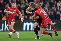 Jeff Hassler of the Ospreys (C) is brought down by Johnny McNicholl of the Scarlets (R) during the Guinness PRO14 Round 6 match between Ospreys and Scarlets at The Liberty Stadium , Swansea, Wales, UK. Saturday 07 October 2017