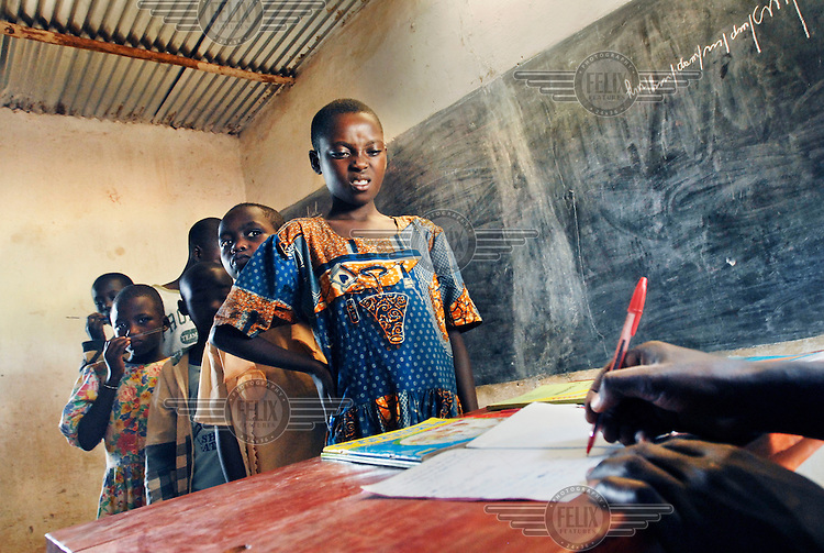Children wait in line to have their notes correctd by their teacher at the Public Prmary School of Butamwa. This school has 985 students, but only 17 teachers. The parents have to pay school fees for their children, up to $3 per trimester, but many struggle to pay this.