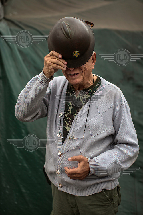 Retired sheriff Alberto Augusto, 72, of the Brazilian Interventionist Resistence Movement (MBRI), who is wearing his grandfather's helmet from 1932, at their headquarters, called PR 1 - Sergeant Mario Kozel Filho Military Interventionist Camp, a radical group that wants military intervention of the government.<br /> <br /> Their headquarters is a makeshift tarpaulin camp situated on an island in the middle of Sergeant Mario Kozel Filho Avenue, between the State Legislative Assembly and the Ministry of the Military.