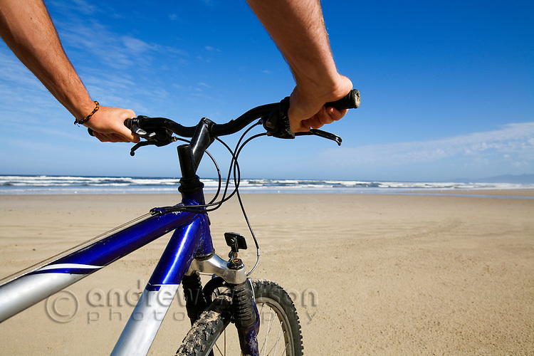 Mountain biking on Ocean Beach.  Strahan, Tasmania, AUSTRALIA