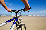 Mountain biking on Ocean Beach.  Strahan, Tasmania, AUSTRALIA