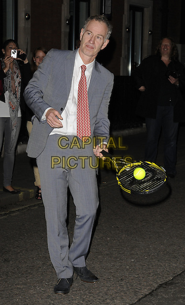 John McEnroe.At the Slazenger Party, The House of St. Barnabas, Greek Street, London, England, UK, 23rd June 2011..full length tennis racquet  grey gray suit red tie white shirt ball playing  .CAP/CAN.©Can Nguyen/Capital Pictures.