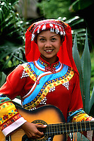 Yunnan woman in traditional costume with guitar in Kumming Chin