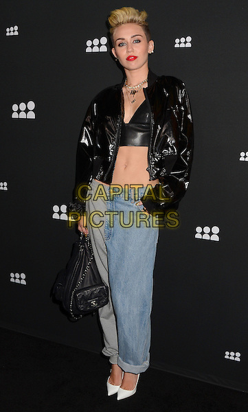 Miley Cyrus<br /> The Myspace Event held at The El Rey Theatre in Los Angeles, California, USA.<br /> June 12th, 2013<br /> full length black leather shiny jacket jeans denim cropped top belly stomach midriff joggers white shoes joggers leg bag purse hand in pocket <br /> CAP/ADM/BT<br /> &copy;Birdie Thompson/AdMedia/Capital Pictures