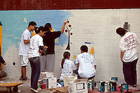 Volunteers with New York Cares paint a mural on the side of PS 33 the Chelsea School in New York City. (© Richard B. Levine)