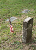A tombstone or grave marker with an United States of America US Flag.