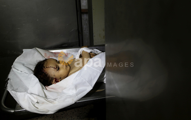 A Palestinian looks at the body of two-year-old girl, Hadeel al-Hadad, at the morgue in the al-Shifa hospital in Gaza City on June 20, 2012. There was no let-up in rocket fire from Gaza with at least 10 hitting the Jewish state despite seven Israeli air strikes overnight, police and the military said. Photo by Ashraf Amra