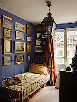 In the blue guest bedroom a collection of paintings and treasured pieces from travels is displayed above the iron bedstead