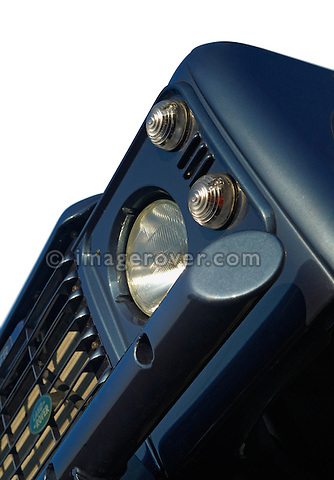 Close up of a blue 2006MY Land Rover Defender TD5 front, vehicle is fitted with a heavy duty bumper and clear indicator glass. White background. --- No releases available. Automotive trademarks are the property of the trademark holder, authorization may be needed for some uses.