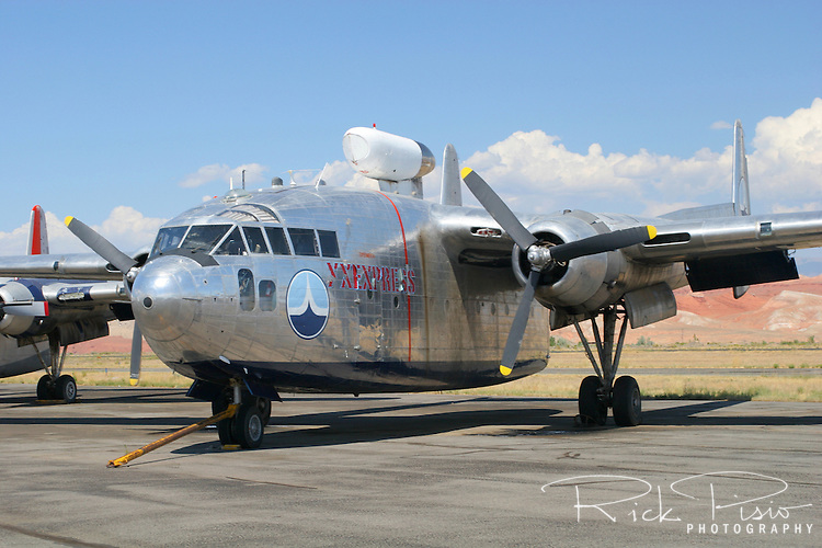 "A C-119 Flying Boxcar, in the livery of the Amaroco Oil Company, that was featured in the opening sequences of the movie ""Flight of the Phoenix"" site on the ramp in Greybull, Wyoming, in August of 2006. The Fairchild built aircraft was sold on August 23rd, 2006 for a reported $70,000 when the assets of Hawkins and Powers were auctioned off. The C-119 made its initial flight in November of 1947 and by the time production ceased in 1955 more than 1,100 of the type had been built. Nicknamed the ""flying boxcar"" for its cargo hauling ability the C-119 was designed to carry cargo, personnel, litter patients, and mechanized equipment. Photographed 08/06"