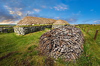 Picture & image peat pile oustide the exterior with stone walls and thatched roof of The historic Blackhouse, 24 Arnol, Bragar, Isle of Lewis, Scotland.