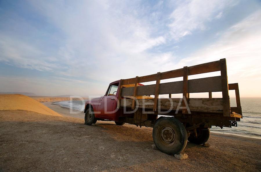 A red farm truck sits on the sand cliffs of Reserva Nacional de Paracas near Paracas and Pisco, Peru.