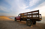 A red farm truck sits on the sand cliffs of Reserva Nacional de Paracas near Paracas and Pisco, Peru.