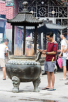 George Town, Penang, Malaysia.  Young Man Preparing Joss Sticks (Incense) outside Goddess of Mercy Temple, Kuan Yin Teng, Kong Hock Keong.