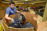 NWA Democrat-Gazette/ANDY SHUPE<br /> Steven Baker, a volunteer associated with HFA, an architecture and engineering firm in Bentonville, helps Saturday, Aug. 4, 2018, to distribute backpacks to children during the 19th annual BackPacks for Kids Day at Samaritan Community Center in Springdale. The organization distributed 3,300 backpacks full of school supplies to children in grades k-12. Parents received a ticket through the Samaritan Community Center Market Food pantry this summer. The event, which happened at both the Springdale and Rogers locations, also featured free haircuts, food and games.