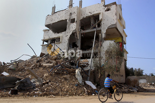 A Palestinian boy rides a bicycle between the rubble of the houses and buildings that were destroyed during the devastating 50-day war between Israel and Hamas at Al-Shojae'ya neighborhood east of Gaza City on October 11, 2014. ahead of a donors conference in Cairo aimed at gathering efforts to the reconstruction of the Gaza Strip after the devastating 50-day war between Israel and the Hamas militants who run the coastal Palestinian enclave. The Palestinian government has unveiled a 76-page reconstruction plan for Gaza, calling for $4 billion to rebuild the war-battered territory, with the largest amount going to build housing for some 100,000 left homeless. Photo by Mohammed Asad