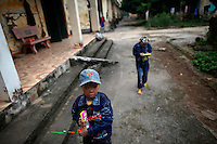 Nguyen Van Khanh (L) and his sister Nguyen Thi An, 13 year old Vietnamese twins suffering from chronic skin illness carry toys in the isolated village of Van Mon south of Hanoi October 24, 2010. Parents left Nguyen Thi An and Nguyen Van Khanh two years ago to live with lepers in Van Mon. More than 600 leprosy affected people live their humble lives with government support in an isolated village founded by French Catholics priests 110 years ago. Leprosy, or Hansen's disease, is caused by the Mycobacterium leprae. It affects the skin, mucous membranes, peripheral nerves and eyes.  REUTERS/Damir Sagolj (VIETNAM)