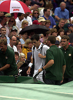 WIMBLEDON CHAMPIONSHIPS 2001 07/07/01 MENS SEMI-FINALS TIM HENMAN  HEADS FOR COVER AS RAIN DELAYS GAME AGAINST GORAN IVANISEVIC PHOTO ROGER PARKER