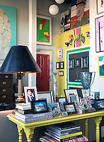 Cluttered but unfussy, a jonquil-yellow table is crammed with family photos and memorabilia in this corner of the vibrant and funky living space