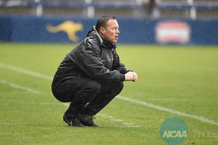 13 DEC 2015: Stanford University Head Coach Jeremy Gunn squats down to watch a play during the Division I Men's Soccer Championship held at Sporting Park in Kansas City, MO.  Stanford defeated Clemson 4-0 for the national title.  Mike Gunnoe/NCAA Photos