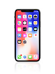 Apple iPhone X, large screen smartphone, product still life with desktop and app icons on its colorful red blue display. The phone is isolated on white studio background with a clipping path.