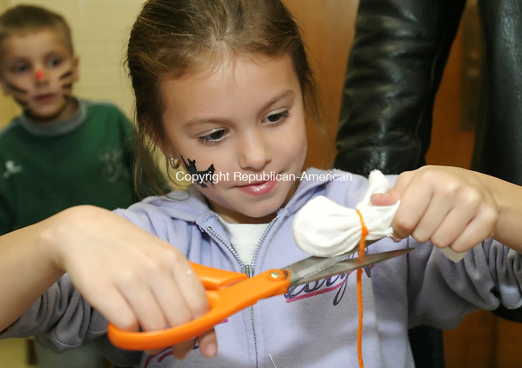 TERRYVILLE, CT 29 October 2005 -102905BZ02- Alyssa Greenlaw, 7, of Terryville, uses a pair of scissors to cut a string while making a ghost during the annual Terryville High School haunted hallway Saturday night.<br /> The event is a fundraiser for the senior class post-graduation party.<br /> Jamison C. Bazinet Republican-American