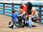"A young boys delivers a tip to two young Musicians playing for tips (""Busking"") on the Oceanside Pier, on visit to Oceanside, CA, on Wednesday, April 27, 2016. Photo by Jim Peppler. Copyright Jim Peppler  2016."