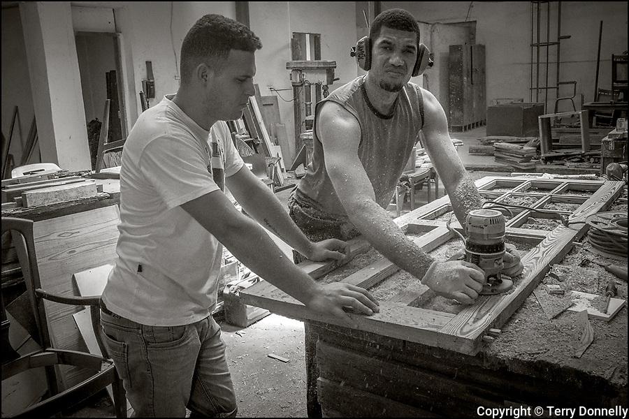 Havana, Cuba:<br /> woodshop with two workers making doors