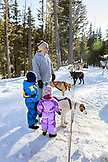 USA, Oregon, Bend, a young boy and girl play with the sled dogs at Mt. Bachelor
