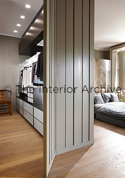 A partition wall with a corrugated finish separates a dressing rooom area from a bedroom.