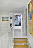 A white hallway at the top of a staircase with painted floorboards. Modern art is displayed on the walls.