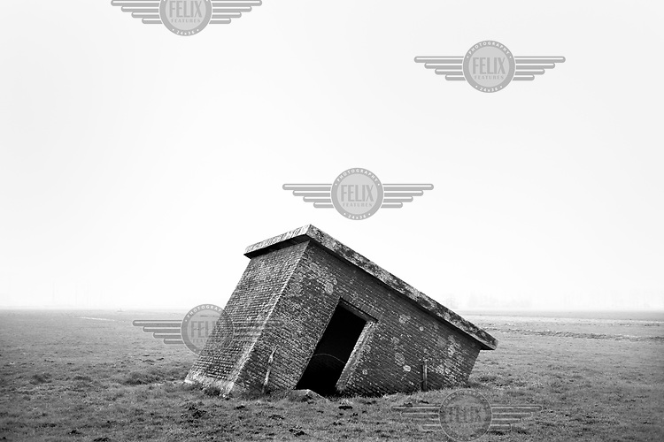 A defensive structure used by the German Army in WWII lies sunken into the ground in a field in the Netherlands along the route of the Atlantic Wall (Atlantikwall in German).The Atlantic Wall (or Atlantikwall in German) was a system of defensive structures built by Nazi Germany between 1942 and 1945, stretching over 1,670 miles (2,690 km) along the coast from the North of Norway to the border between France and Spain at the Pyrenees. The wall was intended to repulse an Allied attack on Nazi-occupied Europe and the largest concentration of structures was along the French coast since an invasion from Great Britain was assumed to be most likely. Slave labour and locals paid a minimum wage were drafted in to supply much of the labour. There are still thousands of ruined structures along the Atlantic coast in all countries where the wall stood except for Germany, where the bunkers were completely dismantled.