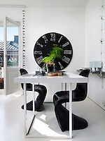 Two curvaceous Verner Panton chairs break up the stark, angular lines of the dining/work area
