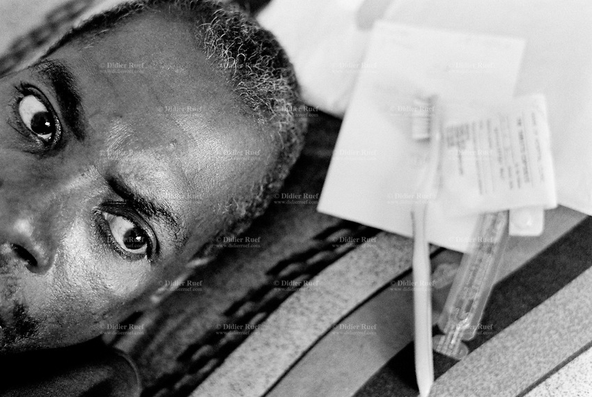 Cameroon. Yaounde. Military hospital. Aids infection. HIV positive patient. Man lying down  in his bed and waiting for a medical consultation. © 2001 Didier Ruef