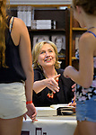 Huntington, New York, U.S. - August 6, 2014 - Hillary Rodham Clinton puts out her arm to shake hands with one of two young girls she's speaking with at the book signing event promoting her new memoir, Hard Choices, at Book Revue in Huntington, Long Island, during a nationwide tour. Clinton's book is about her four years as America's 67th Secretary of State and how they influence her view of the future.