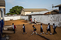 MONROVIA, LIBERIA - FEBRUARY 17: Students walk to class after morning assembly on the second day of school, since schools closed due to the Ebola outbreak 6 months ago, at the C.D.B. King Elementary School on February 17, 2015 in Monrovia, Liberia. Though Ebola cases have receded into the single digits in Liberia, lingering fear and a depressed economy have dampened the turnout at schools. Many have yet to reopen, having failed to meet the minimum requirements put in place to prevent the transmission of the virus. Many of those that have reopened &ndash; like C.D.B. King, which, though located in the center of the capital, lacks electricity and running water, and has only a few toilet stalls for a student population that numbered 1,000 before Ebola &mdash; are struggling. <br /> Daniel Berehulak for The New York Times