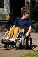 Young woman in wheelchair attempting to manuever onto sidewalk without handicap access. Birmingham Alabama.