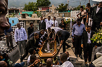 Friends and family attend the funeral of Carlos, 26, who died from a fever, in the Grand Cemetery on November 11, 2017 in Port-au-Prince, Haiti. Death is a particularly plentiful resource here. Haitians' life expectancy is only 63.4 — almost 12 years below the Latin America and Caribbean average.<br /> <br /> The funeral homes offer many packages to mourners. The most ornate service comes with a limousine and bus for guests. It runs around $8,000. Few in Haiti have that kind of money. Most take a cheaper option, which still includes professional photos, a hearse, flowers and a small brass band called a fanfa to serenade the corpse in its open coffin and lead the procession to the cemetery.<br /> <br /> Even with the cheapest option, many poor people go into debt to pay for a loved one's funeral. Others opt for shame rather than crippling debt, and never go through with the service. The Louises have always had a problem of customers abandoning their loved ones in their cold rooms.<br /> Photo Daniel Berehulak for The New York Times
