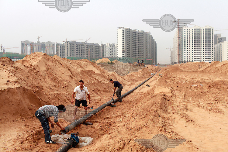 A small construction crew lays water pipes through the arid land surrounding a new apartment development. Like many coal rich regions in China's arid northwest, a vast amount of mineral wealth has been re-invested into the local economy in the form of speculative real estate ventures, creating hundreds of new cities many containing very few real residents.