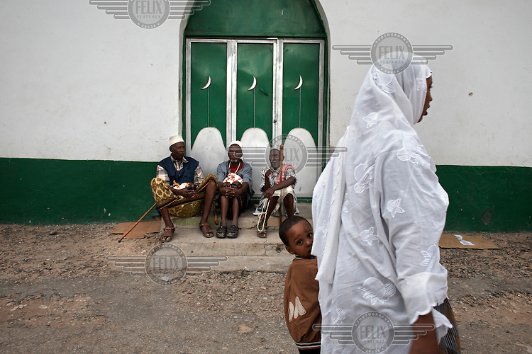 Men relax outside a mosque in Hargeisa as a woman and child pass by.