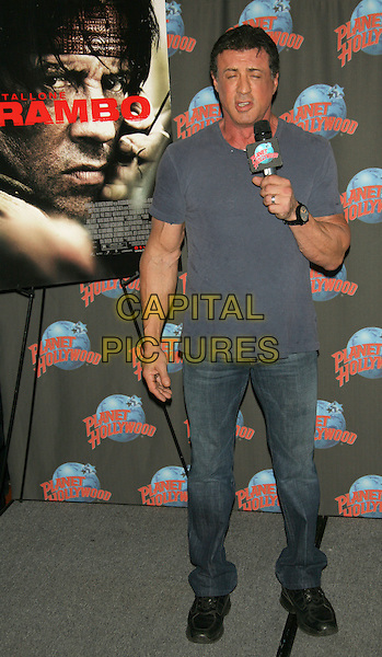 "SYLVESTER STALLONE.Movie memorabilia donation event to promote the 4th installment of ""Rambo"" at Planet Hollywood Times Square, New York, NY, USA..January 17th, 2008.full length grey gray tee shirt microphone funny jeans denim .TOM/CAP/LNC.©TOM/LNC/Capital Pictures"