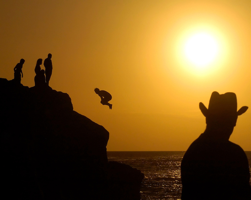 A cowboy tourist watches as locals jump from a cliff in Waimea Bay, Hawaii. During the flat days of summer, surfers and other ocean adventures look to other thrills on the north shore of Hawaii..(James J. Lee)