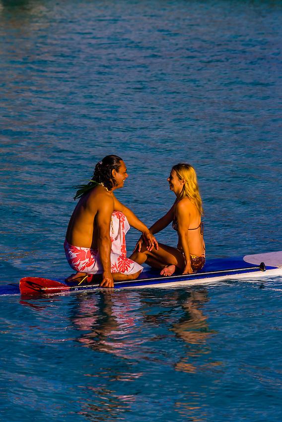 A couple rowing around the lagoon on a paddleboard, Four Seasons Resort Bora Bora, French Polynesia.