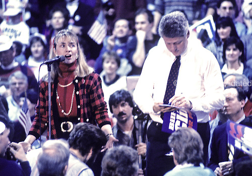 """Hillary Rodham Clinton, left, speaks at a campaign rally at Fairgrounds Junior High School in Nashua, New Hampshire as her husband, Governor Bill Clinton (Democrat of Arkansas), right, signs autographs on February 16, 1992.  The Clintons were campaigning in advance of New Hampshire's """"First in the Nation"""" presidential primary.<br /> Credit: Ron Sachs / CNP"""