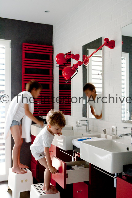 The boys' bathroom is cheerfully decorated with accents of red, black and white