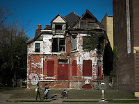 People walks  as a man rests in a street in front of a abandoned house in Detroit, the city has more than 16 months of filing for bankruptcy.  10.24.2014. Teddy Blackburn /VIEWpress