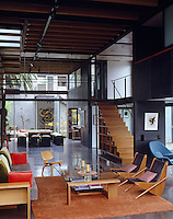An open staircase made of walnut leads down from a glass and steel tension bridge spanning the width of the spacious living area