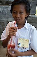 Bali, Indonesia.   Teenage Schoolgirl with a Juice Drink.  Tenganan Village.