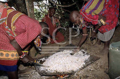 Lolgorian, Kenya. Siria Maasai; women preparing maize beer; preparing the milled maize, roasting over an open fire.
